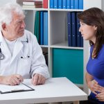 Young woman with stomachache visiting senior doctor