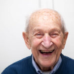 Senior adult male portrait; he is 90 years old. In front of his out of focus white kitchen wall.
